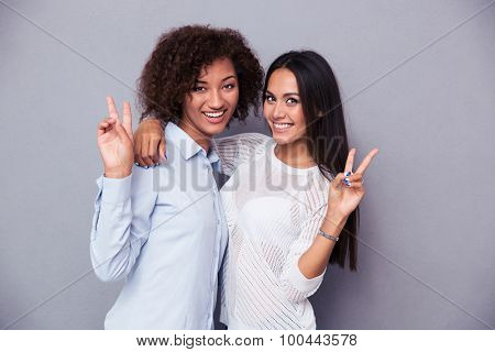 Portrait of a two girlfriends showing two fingers sign on gray background and looking at camera