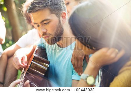Group of a young friends with guitar having fun outdoor