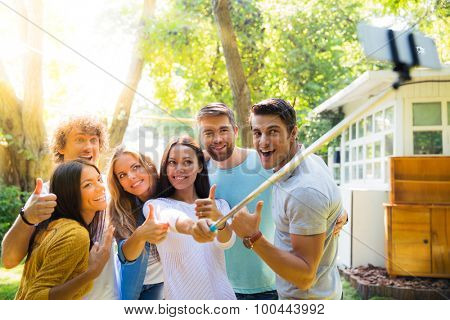 Happy friends making selfie photo outdoors