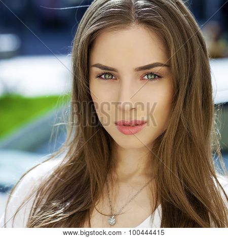 Portrait of a young brunette woman on summer street