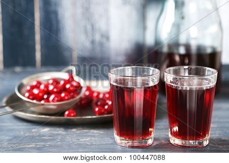Sweet homemade cherry juice on table, on color wooden background