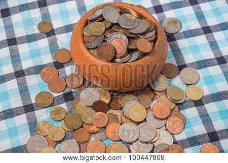 Pile Of Coins Baht Currency Is Poured Out The Pottery Cup On The Loincloth Silk Background.