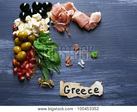 Map of Greece made with ingredients of traditional Greek cuisine on color wooden background