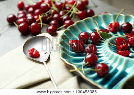 Sweet cherries on plate, on dark background
