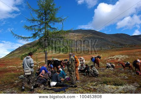 Group of tourists resting on the mountain pass.