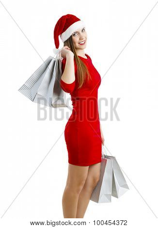 Beautiful and attractive woman with a santa hat holding shopping bags