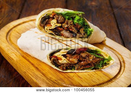 Burritos With Pork, Mushrooms And Vegetables At Wooden Desk