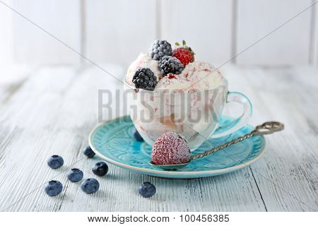 Delicious ice cream with fresh frozen berries, on color wooden background