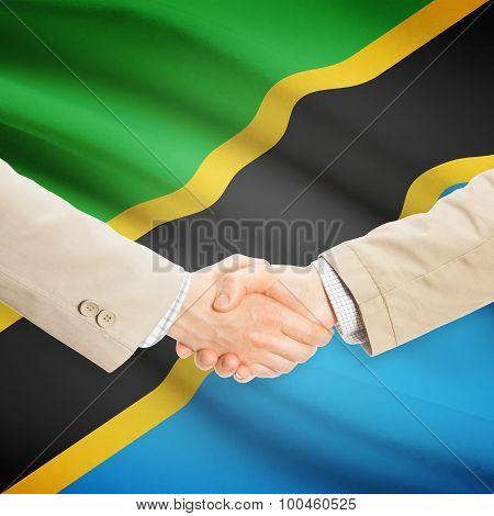 Businessmen Handshake With Flag On Background - Tanzania
