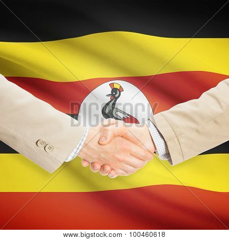Businessmen Handshake With Flag On Background - Uganda