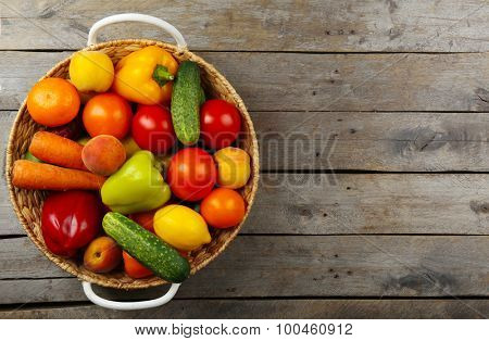 Heap of fresh fruits and vegetables in basket on wooden table close up