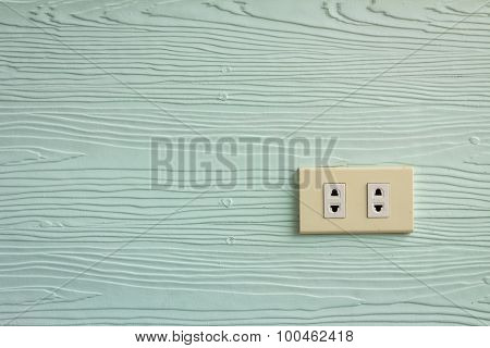 Wall Outlets On The Pale Green Wall With Wood Texture