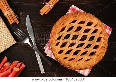 Strawberry rhubarb pie overhead scene on dark wood