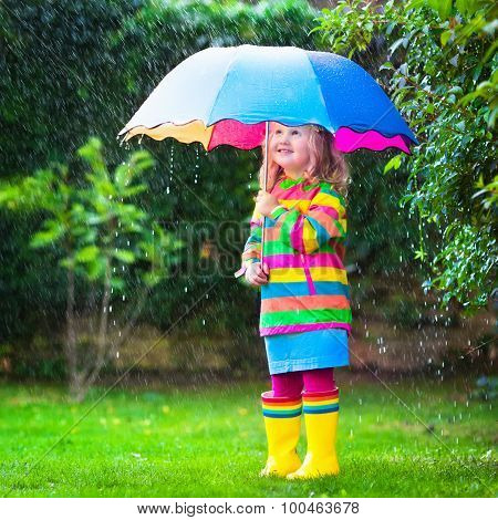 Little Girl Playing In The Rain Under Colorful Umbrella