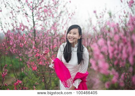 Beautiful Vietnamese girl with traditional dress (ao dai) is in peach flower garden in Vietnam