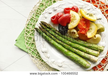 Roasted asparagus and tasty colorful pasta with vegetables on plate on wooden table background