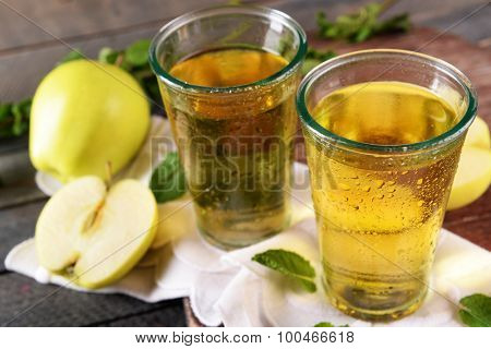 Wet glasses of apple juice on wooden table, closeup