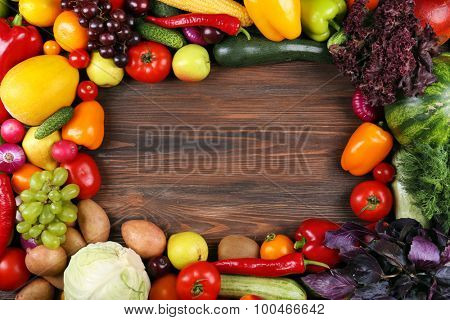 Heap of fruits and vegetables on wooden background
