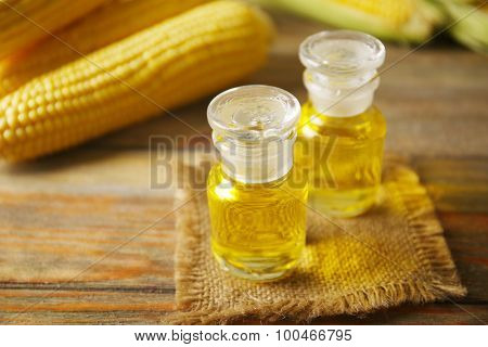 Fresh corn with bottles of oil on table close up