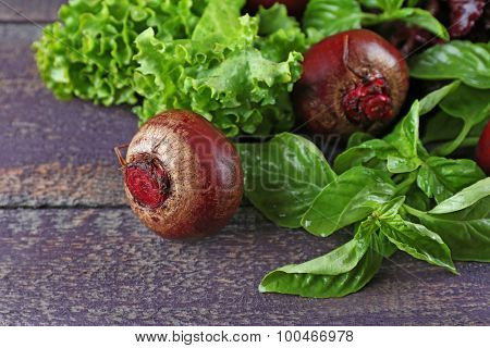 Red beets with greens on wooden table close up