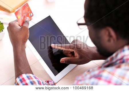 African American male hands with tablet and credit card at workplace