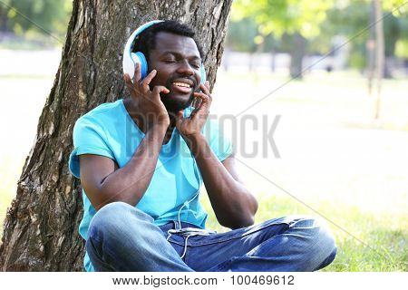 African American man with headphones near tree in park