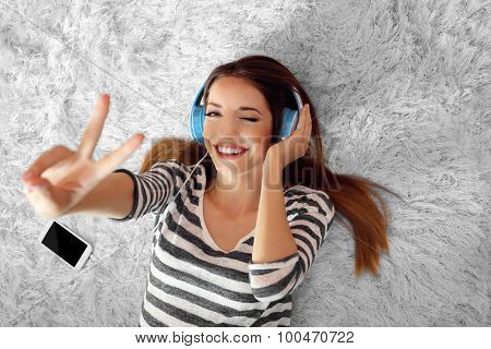 Woman listening music in headphones on carpet in room