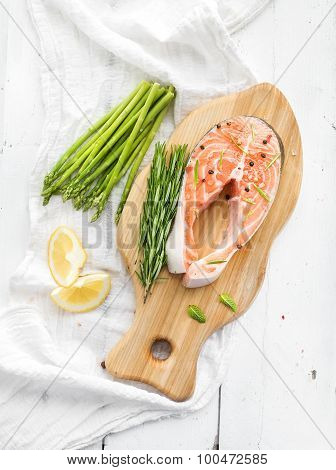 Raw salmon steak with asparagus, lemon, spices and rosemary on rustic wooden chopping board over whi