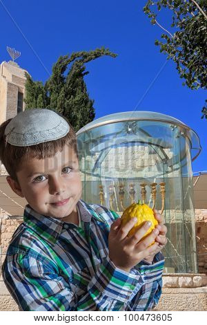 Cute seven year old boy in a white skullcap with the etrog. Sukkot at the Golden Menorah in Jerusalem