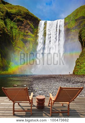 Magnificent powerful jet Sk�³gar River forms a large rainbow. The famous waterfall Sk�³gafoss, Iceland. On stony ground in front of the waterfall are two wooden deck chairs