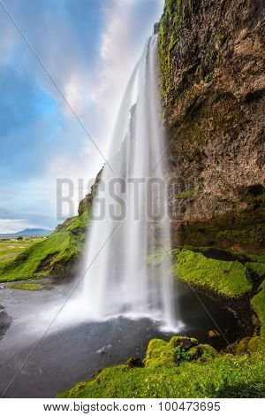 Sunny day in Iceland. Seljalandsfoss waterfall in July. Passage under the waterfall