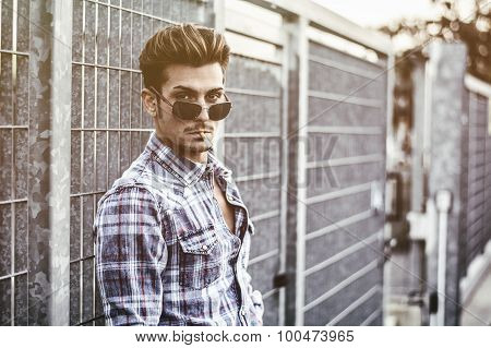 Trendy cool young man standing outside, leaning against metal gate