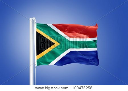 Flag of South Africa flying against a blue sky.