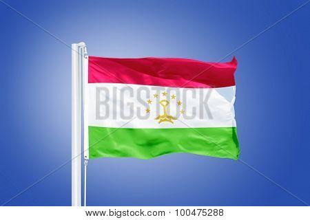 Flag of Tajikistan flying against a blue sky.