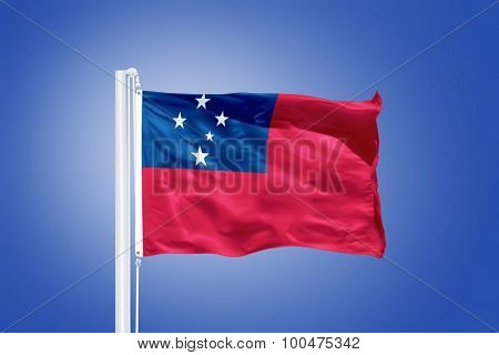 Flag of Samoa flying against a blue sky.