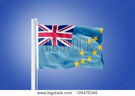 Flag of Tuvalu flying against a blue sky.