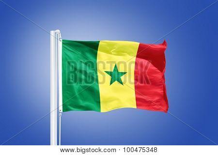 Flag of Senegal flying against a blue sky.