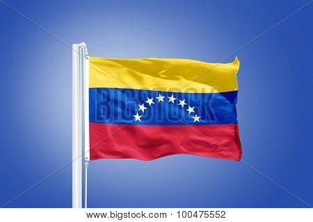 Flag of Venezuela flying against a blue sky.