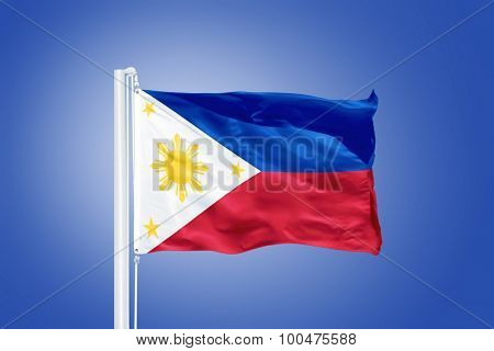 Flag of Philippines flying against a blue sky.