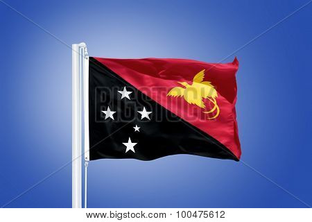 Flag of Papua New Guinea flying against a blue sky.