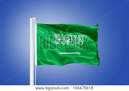 Flag of Saudi Arabia flying against a blue sky.