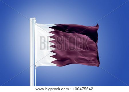 Flag of Qatar flying against a blue sky.