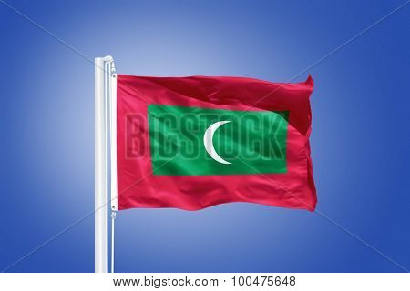 Flag of Maldives flying against a blue sky.