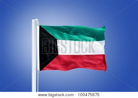 Flag of Kuwait flying against a blue sky.
