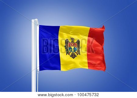 Flag of Moldova flying against a blue sky.