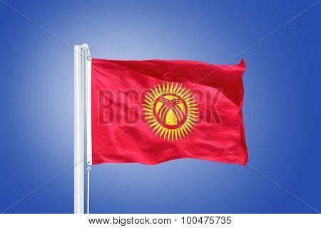 Flag of Kyrgyzstan flying against a blue sky.