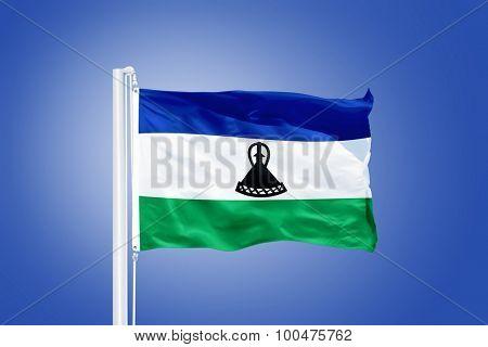 Flag of Lesotho flying against a blue sky.