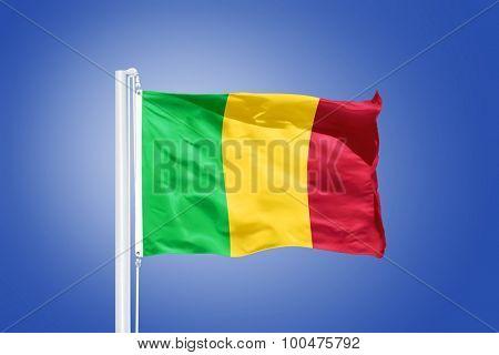 Flag of Mali flying against a blue sky.