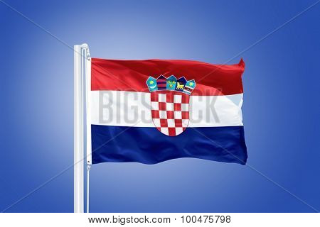 Flag of Croatia flying against a blue sky.
