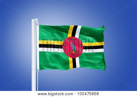 Flag of Dominica flying against a blue sky.
